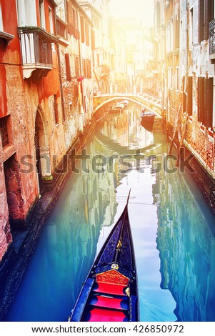 Sailing gondola and the beautiful narrow canal in Venice, Italy. - stock photo