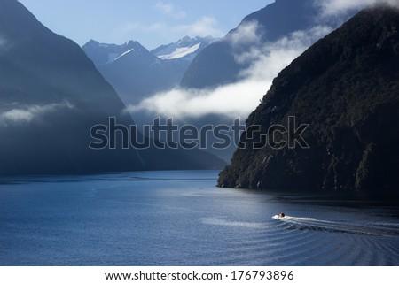 Sailing into Milford Sound on South Island of New Zealand in early morning as the sun rises above the mountains - stock photo