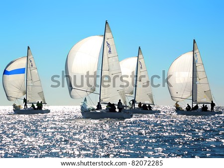 Sailing regatta in Greece: Four back-lighted boats with spinnakers open - stock photo