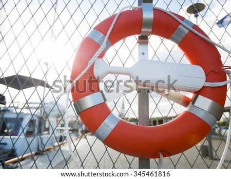 sailing, safety and life rescuing concept - lifebuoy hanging on fence over moored boats on pier - stock photo