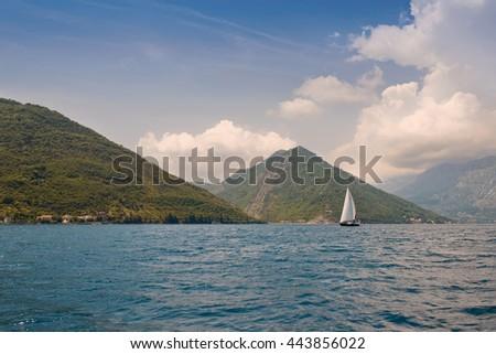 Sailing ship in sunny day at Boka Kotor bay (Boka Kotorska), Montenegro, Europe. Yacht with white sails on the Adriatic Sea. Marine trip, beautiful seascape.  - stock photo