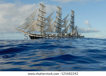 Sailing ship in the ocean with small waves is getting all the sails filled with sea breeze - stock photo