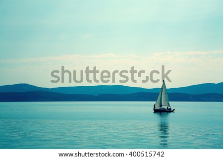 sailing ship on a mountain lake in good weather on a background of blue sky. nature background. yachting