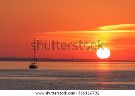 Sailing ship on the background of orange sunset - stock photo
