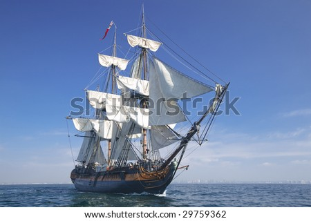 Sailing ship under sail breaking through the waves. - stock photo