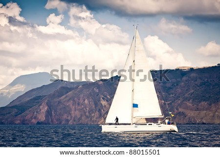 Sailing ship yacht with white sail in open sea. Rocks in the background - stock photo