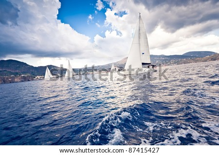 Sailing ship yachts with white sails in a row - stock photo