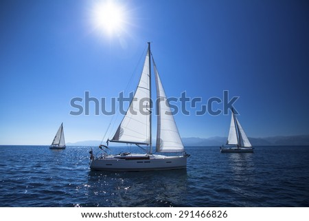 Sailing ship yachts with white sails in the open Sea. Noon, the blue sky and the Sun at the Zenith. - stock photo