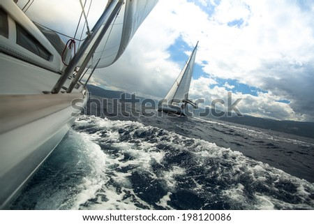 Sailing ship yachts with white sails in the sea in stormy weather. - stock photo