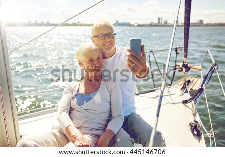 sailing, technology, tourism, travel and people concept - happy senior couple with smartphone taking selfie on sail boat or yacht deck floating in sea - stock photo