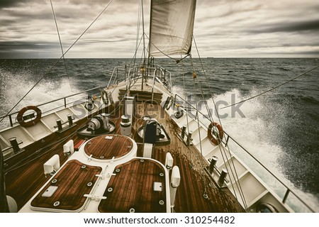 Sailing yacht at sunset during a storm. Toned image and blur. Retro style postcard. Sailing. Yachting. Travel - stock photo