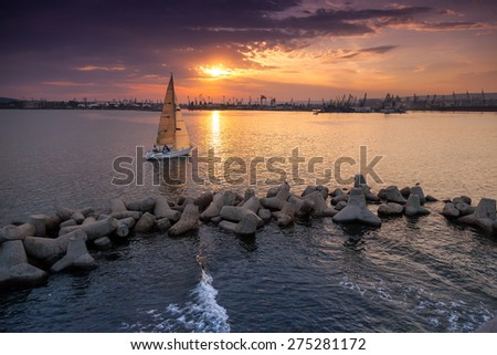 Sailing yacht enters the Varna harbor at the sunset. Black Sea coast - stock photo