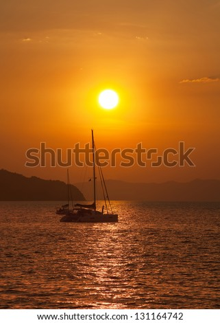 Sailing yacht illuminated by the light of the sun setting - stock photo