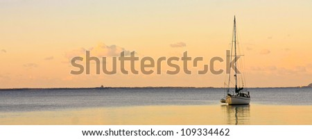 Sailing yacht on water at sunset