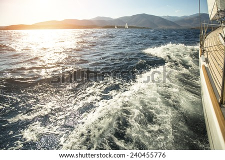 Sailing. Yacht sailing towards the sunset. Luxury yachts. - stock photo