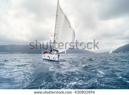 """Sailing yacht with flying. Tivat, Montenegro - 26 April, 2016. Regatta """"Russian stream"""" in God-Katorskaya bay of the Adriatic Sea off the coast of Montenegro. - stock photo"""