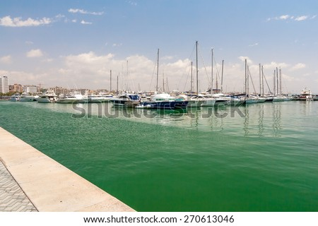 Sailing yachts and boats are in the harbor Palma de Mallorca. . Yacht standing at the pier without sails. Quiet sunny summer day. In a calm green water reflected the yacht. In the sky clouds float. - stock photo