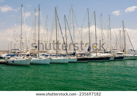 Sailing yachts are in port. Sailing yachts are in port. Many masts against the blue sky. - stock photo