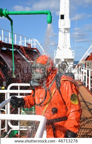 sailor in a protective suit washes himself in the safety shower after  cleaning operations in the cargo tank on a chemical tanker - stock photo