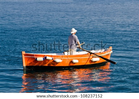 Sailor rowing on wooden taxi boat in Zadar, Croatia - stock photo