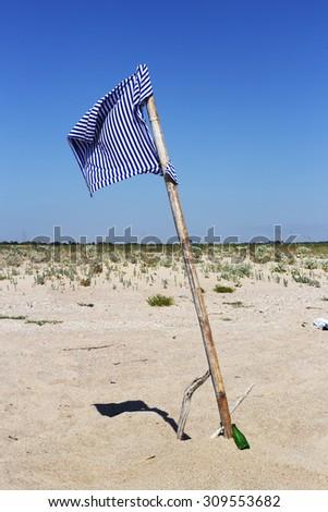 Sailor T-shirt as a flag on a deserted beach - stock photo