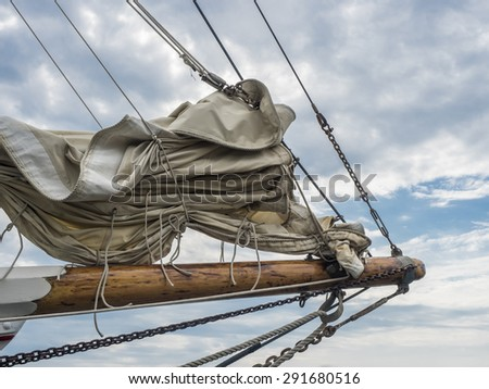 Sails furled on bow sprint of a vintage sailing ship. - stock photo