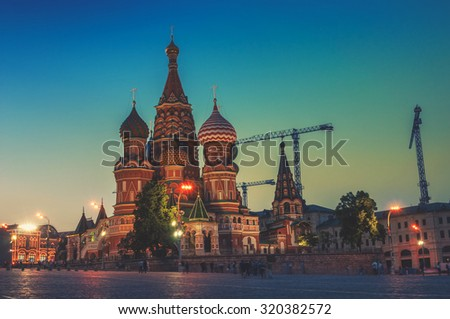 Saint Basil Cathedral in Moscow, Russia on Red Square at sunset, colorful clear sky. Blurred people and pebble pavement at the foreground - stock photo