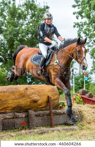 Saint Cyr du Doret, France - July 29, 2016: Woman riding horse over obstacle on cross country event