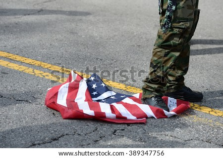 Saint Louis, MO, USA - March 11, 2016: Protester desecrates flag outside a Donald Trump rally in the Peabody Opera House in Downtown Saint Louis - stock photo