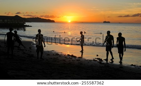 SAINT LUCIA, CARIBBEAN - DECEMBER 10, 2014: Tourists play football at sunset in the exotic resort of Saint James Club.