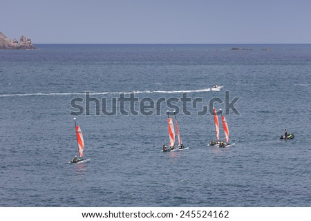 SAINT-MALO, FRANCE - JULY 6, 2011: Group of teenagers learning catamaran sailing on the coast of Saint-Malo. The hull length of their Topaz 12 catamarans is 3.65m. - stock photo