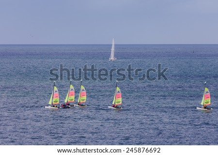 SAINT-MALO, FRANCE - JULY 6, 2011: Group of teenagers learning catamaran sailing on the coast of Saint-Malo. Their Hobie Cat Teddy catamarans are 13 feet long and have a great buoyancy. - stock photo