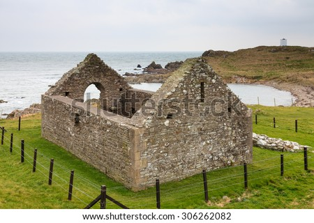 Saint Ninian's Chapel.  A view of Saint Ninian's chapel in the Isle of Whithorn in Dumfries and Galloway, Southern Scotland.  In the background can be seen the Isle of Whithorn Tower. - stock photo