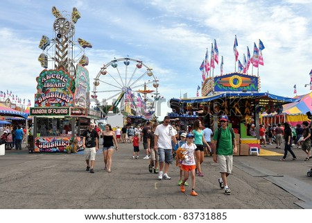 SAINT PAUL - AUGUST 27:  People walk through the midway at the Minnesota State Fair on Aug. 27, 2011 in St. Paul, Minnesota. Attendance averages about 140,000 per day in 2011. - stock photo