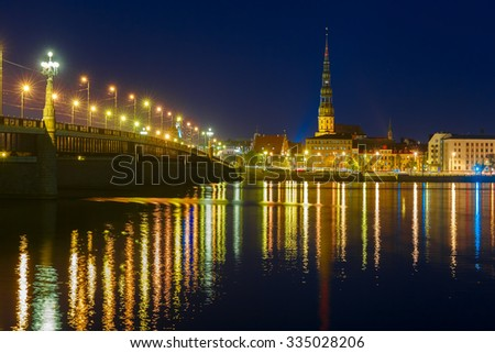 Saint Peter church, Stone Bridge and River Daugava in the Old Town of Riga at night, Latvia - stock photo