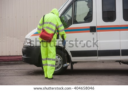 Saint-Petersburg, Russia - April 6, 2016: A man in a special protective suit green measures the level of radiation on the car after a decontamination treatment. - stock photo