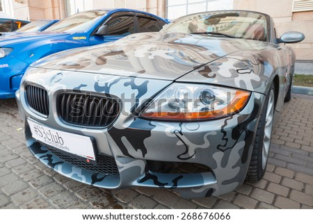Saint-Petersburg, Russia - April 11, 2015: BMW z4 roadster car with camouflage color scheme stands parket on the street, closeup photo