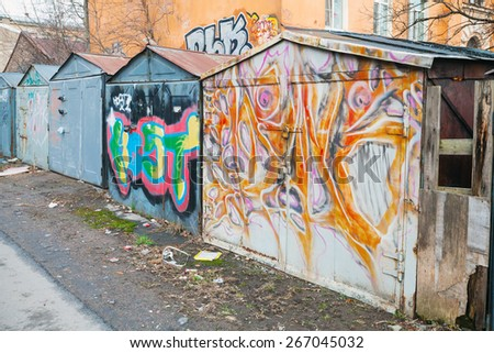 Saint-Petersburg, Russia - April 3, 2015: Old rusted locked abandoned garages with colorful grungy graffiti. Vasilievsky island, Central old part of St. Petersburg city - stock photo