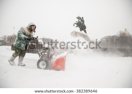 Saint-Petersburg, Russia - January 12, 2016: A man cleaning an area using a petrol snow thrower in the historic tourist center of the city near the monument to Tsar Peter the first - stock photo