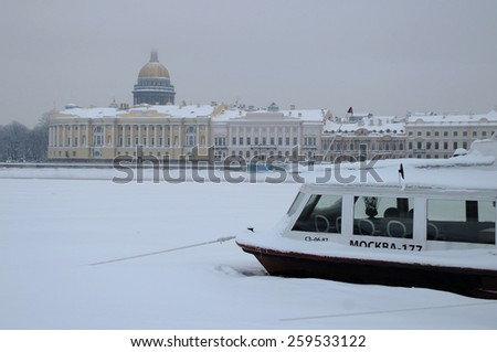 SAINT PETERSBURG, RUSSIA - JANUARY 9, 2009: View of Saint Isaac's Cathedral, the frozen Neva river and ice-bound motor boat on a gloomy foggy winter day - stock photo