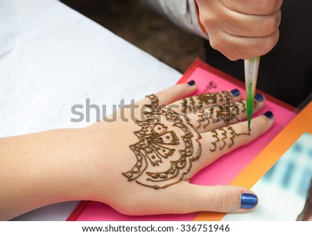 Saint-Petersburg, Russia - July 19, 2015: Brown henna paste or mehndi application on woman hand, traditional Indian natural skin decoration or bio-tattoo