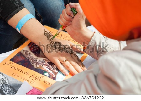 Saint-Petersburg, Russia - July 19, 2015: mehndi application on woman palm, traditional Indian natural skin decoration or bio-tattoo