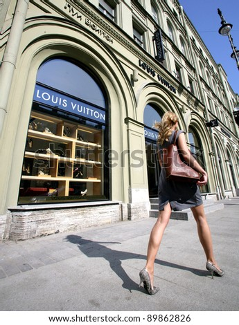 SAINT PETERSBURG, RUSSIA - JUNE 15: An upscale shopper walk by a Louis Vuitton store in Saint Petersburg, Russia on Wednesday, June 15, 2011