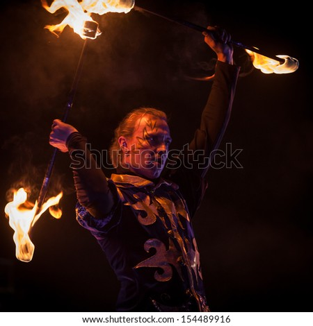"SAINT-PETERSBURG, RUSSIA - SEPTEMBER 14, 2013 : A man  dances with two fire staffs on ""Alive Fires"" festival"