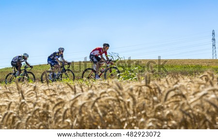 SAINT-QUENTIN-FALLAVIER,FRANCE - JUL 16: Three cyclists (Lars Bak ,Petr Vakoc and Natnael Berhane ) riding in a wheat plain during the stage 14 of Tour de France 2016.