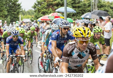SAINT REMY DE PROVENCE, FRANCE - JUL 20:The peloton rides on a wet slippery road curve in Saint Remy de Provence during the stage 15 of Le Tour de France on July 20 2014
