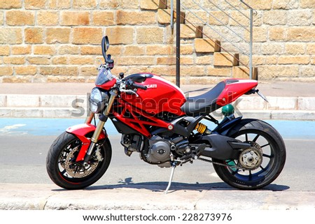 SAINT-TROPEZ, FRANCE - AUGUST 3, 2014: Red motorcycle Ducati Monster at the city street. - stock photo