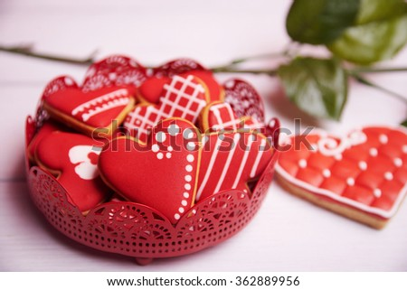 Saint Valentine card. Heart shaped gingerbread over rustic wooden background. With red rose. Close view