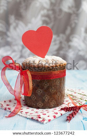 Saint Valentine's cake with red heart on the wooden table (panettone) - stock photo