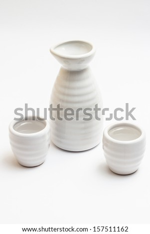Sake bottle decorated with sakura and colored drinks - stock photo